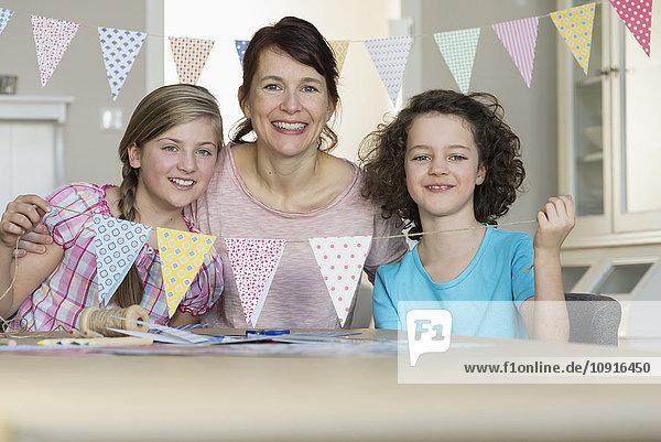 Glückliche Mutter und Töchter mit Papiergirlande
