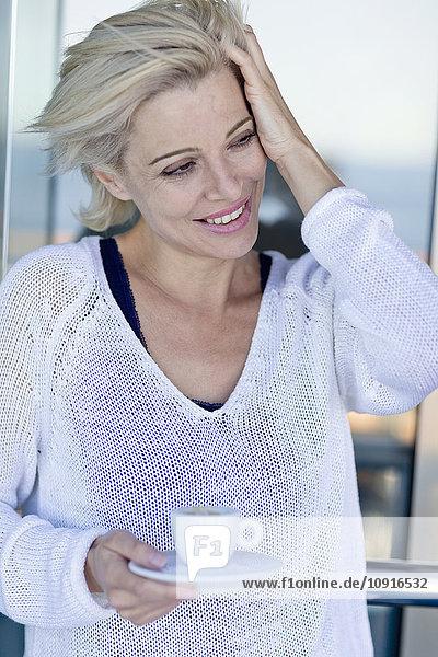 Reife Frau mit einer Tasse Kaffee  während der Kreuzfahrt