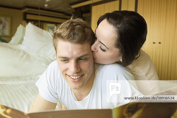 Junges Paar auf Kreuzfahrt auf dem Bett liegend