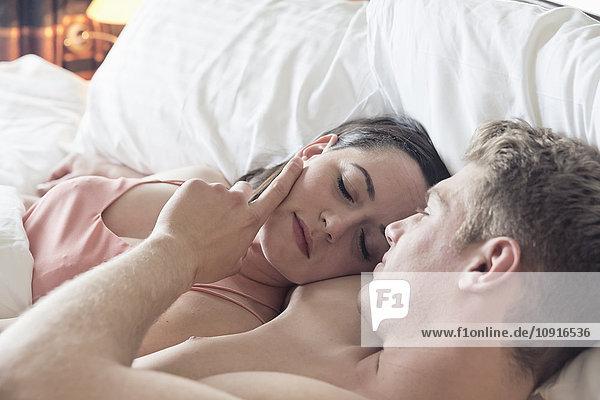 Junges Paar im Bett liegend kuschelnd