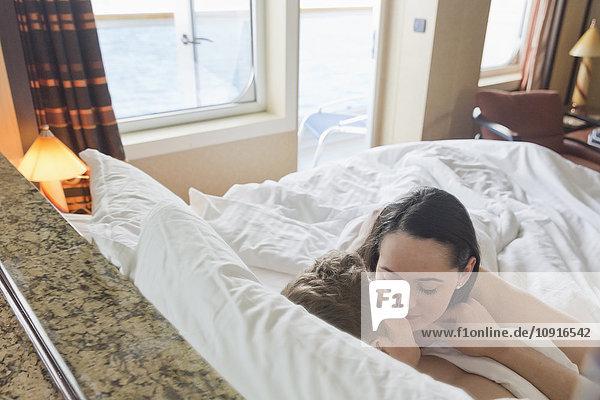 Junges Paar auf Kreuzfahrt kuscheln im Bett