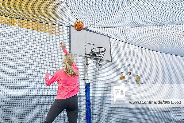 Frau spielt Basketball auf dem Deck eines Kreuzfahrtschiffes