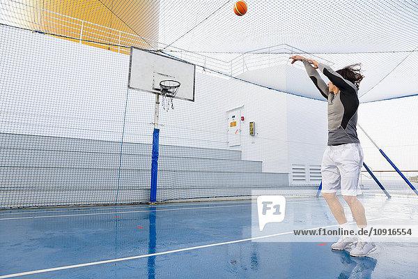 Junger Mann spielt Basketball auf dem Deck eines Kreuzfahrtschiffes