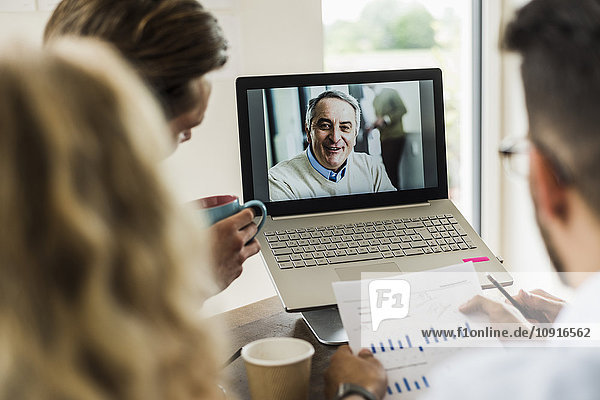 Colleagues having a video conference in office
