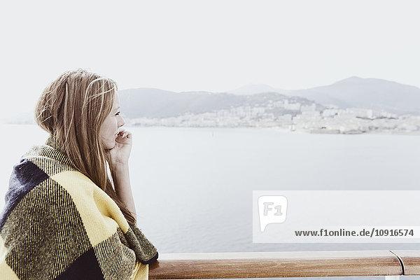 Blonde Frau mit Decke an Deck eines Kreuzfahrtschiffes mit Blick auf die Ferne