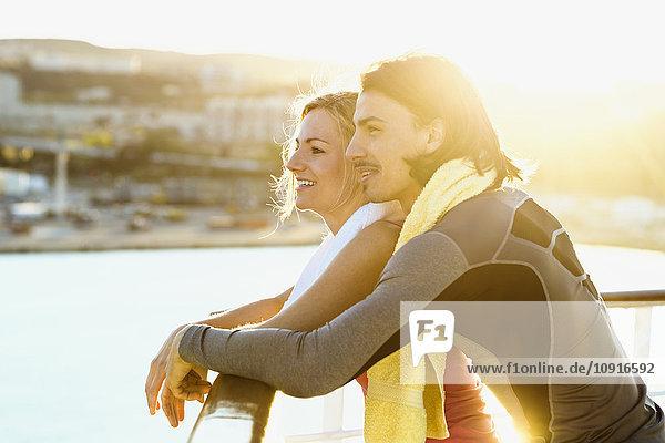 Ein glückliches Paar steht auf dem Deck eines Kreuzfahrtschiffes und schaut in die Ferne.