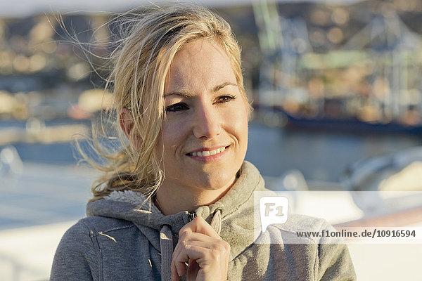 Porträt einer lächelnden blonden Frau an Deck bei Sonnenlicht