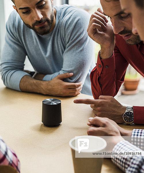 Kollegen am Tisch mit rundem Gegenstand diskutieren