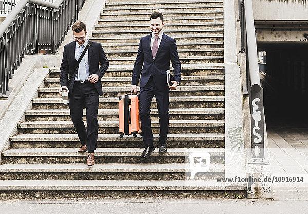 Geschäftsleute auf Geschäftsreise  die mit Rollgepäck die Treppe hinuntergehen.