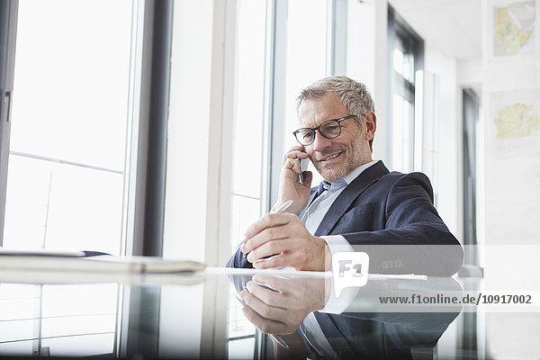 Erfolgreicher Geschäftsmann im Büro beim Telefonieren