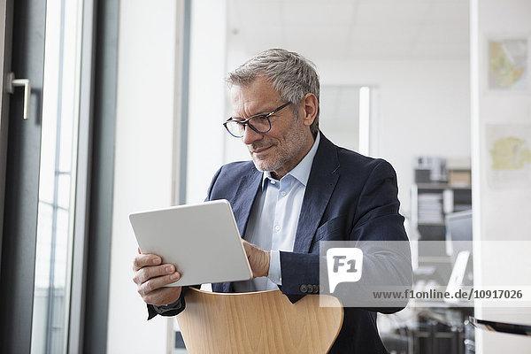 Erfolgreicher Geschäftsmann in seinem Büro mit digitalem Tablett