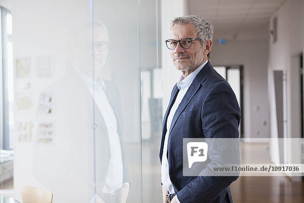 Successful businessman standing in his office looking out of window