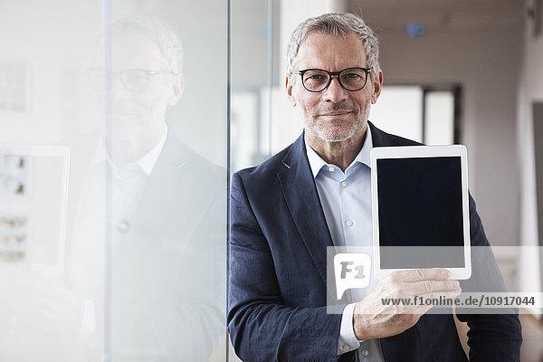 Erfolgreicher Geschäftsmann mit digitalem Tablett im Büro