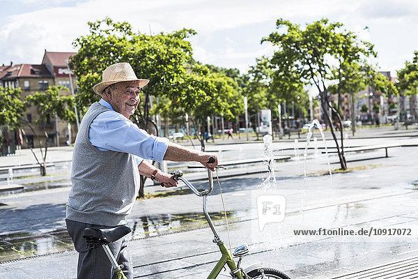 Lächelnder älterer Mann mit klappbarem Fahrrad
