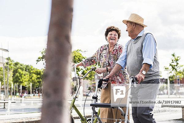 Seniorenpaar mit Fahrrad und Rollator