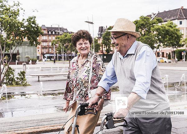 Älterer Mann  der mit seiner Frau auf Rädern spazieren geht.