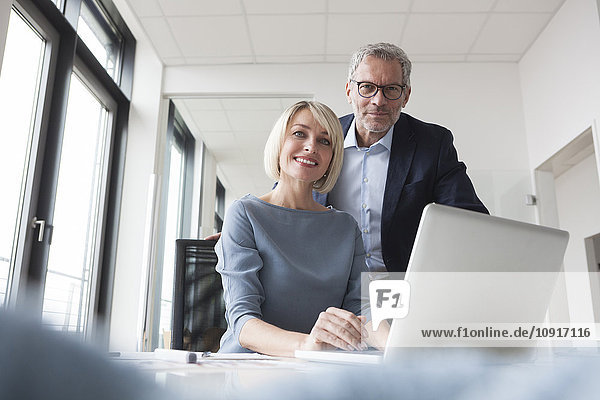 Geschäftsmann und Frau arbeiten zusammen im Büro mit Laptop