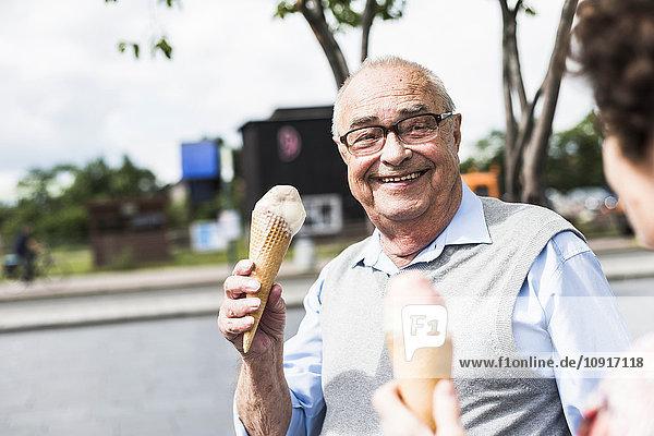 Porträt eines glücklichen älteren Mannes mit Eistüte  der seine Frau ansieht.