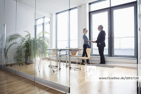Geschäftsmann und Frau im Büro beim Händeschütteln