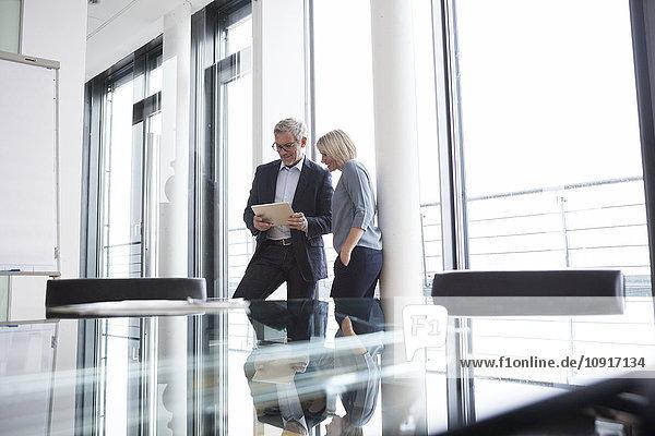 Geschäftsmann und Frau im Büro beim Betrachten des digitalen Tabletts