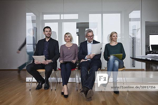 Vier Leute sitzen in einer Reihe und warten im Büro.
