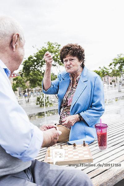Porträt einer älteren Frau  die auf einer Bank sitzt und mit ihrem Mann Schach spielt.