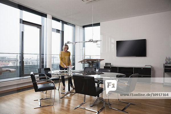 Businesswoman preparing for conference in board room