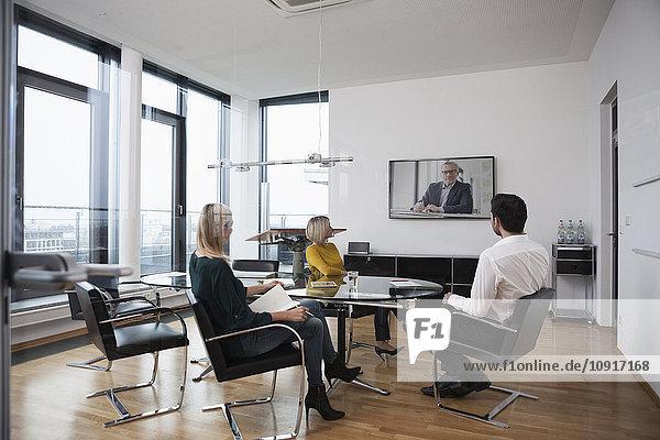 Geschäftsleute mit einer Videokonferenz im Sitzungssaal