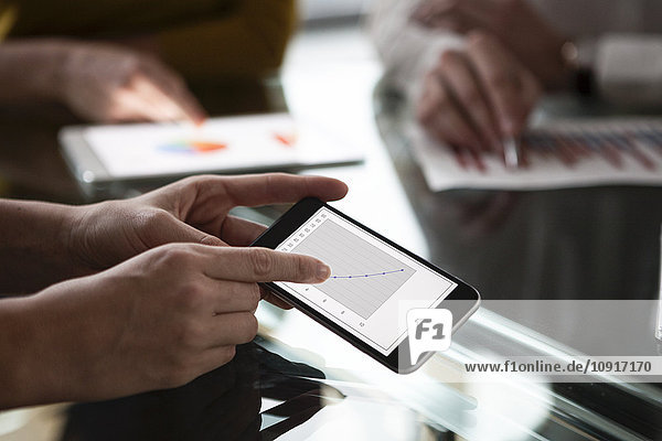 Geschäftsleute bei Besprechungen im Büro mit portablen Geräten