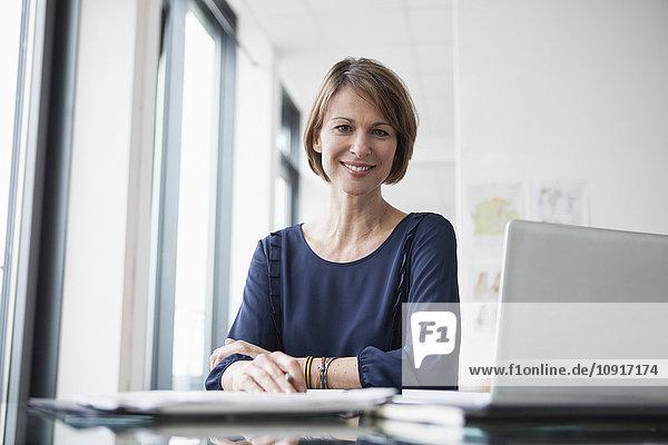 Porträt der lächelnden Geschäftsfrau am Schreibtisch
