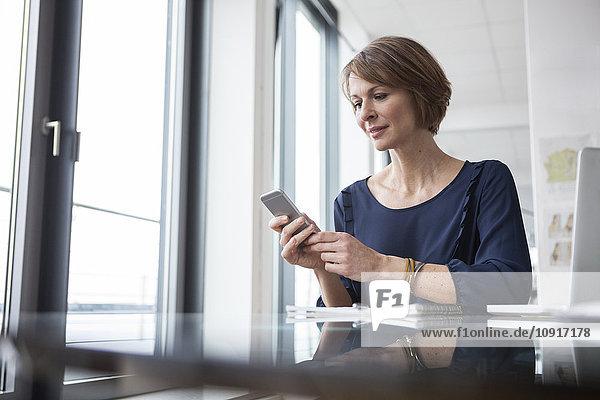 Geschäftsfrau auf dem Handy am Schreibtisch