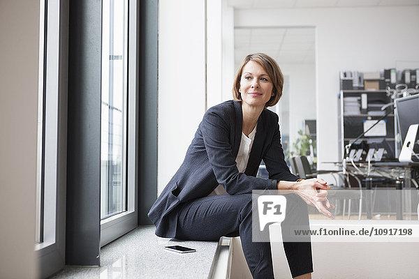 Geschäftsfrau am Fenster sitzend