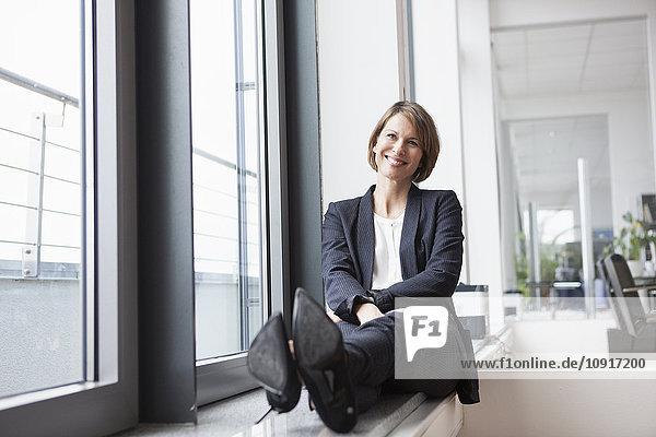 Entspannte Geschäftsfrau am Fenster sitzend
