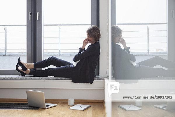 Lächelnde Geschäftsfrau sitzt am Fenster und schaut auf den Laptop.