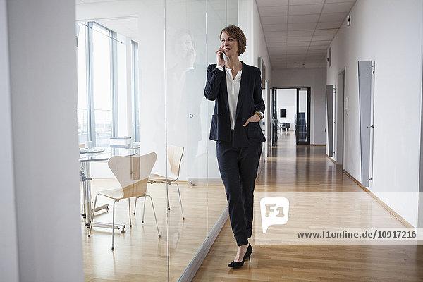 Geschäftsfrau am Handy in der Bürohalle