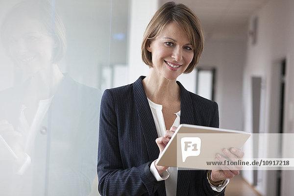 Lächelnde Geschäftsfrau mit digitalem Tablett im Büro