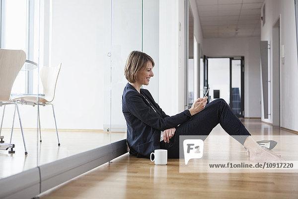 Geschäftsfrau ruht auf der Büroetage mit Blick auf das Handy