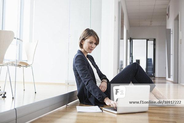 Geschäftsfrau sitzend auf Büroetage mit Laptop