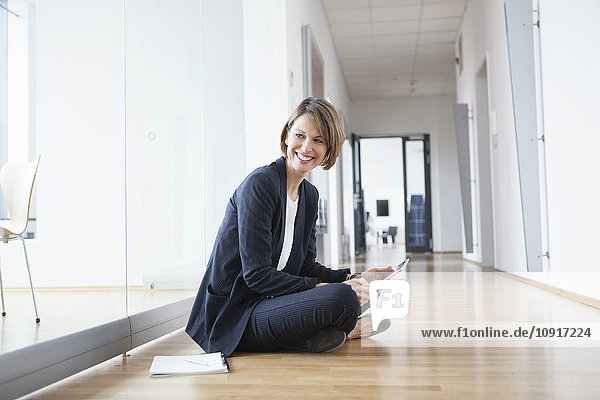 Lächelnde Geschäftsfrau sitzt im Büro und hält ein digitales Tablett.