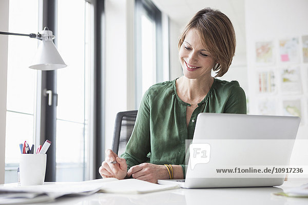 Lächelnde Geschäftsfrau bei der Arbeit am Schreibtisch
