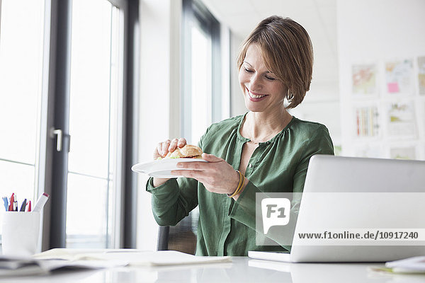 Lächelnde Geschäftsfrau bei der Mittagspause am Schreibtisch