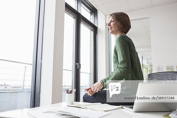 Geschäftsfrau auf dem Schreibtisch mit Blick aus dem Fenster