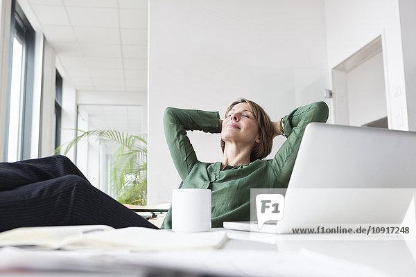 Geschäftsfrau entspannt am Schreibtisch