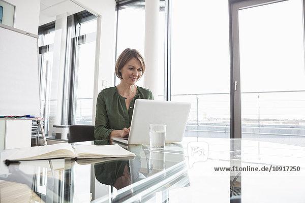 Lächelnde Geschäftsfrau bei der Arbeit am Laptop am Schreibtisch