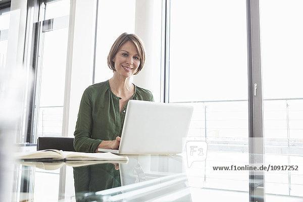 Porträt einer lächelnden Geschäftsfrau  die am Schreibtisch am Laptop arbeitet.