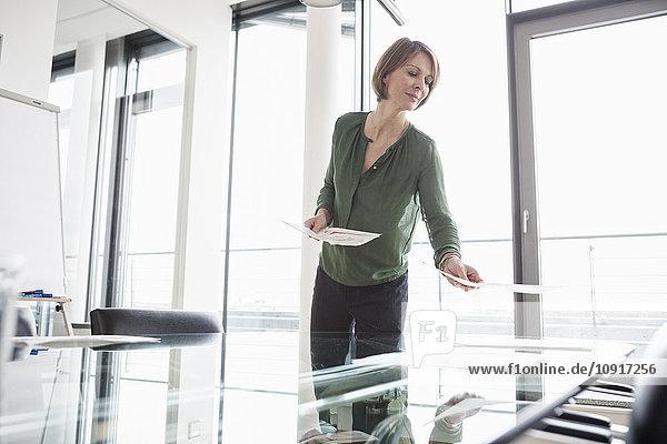 Geschäftsfrau beim Verteilen von Dokumenten im Konferenzraum