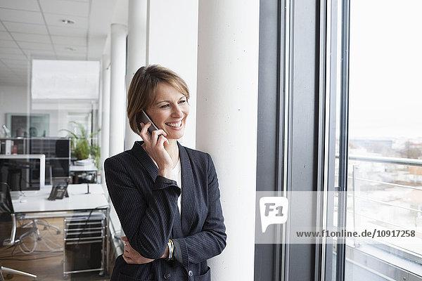 Lächelnde Geschäftsfrau am Handy am Fenster