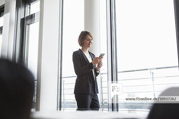 Lächelnde Geschäftsfrau beim Blick auf das Handy am Fenster