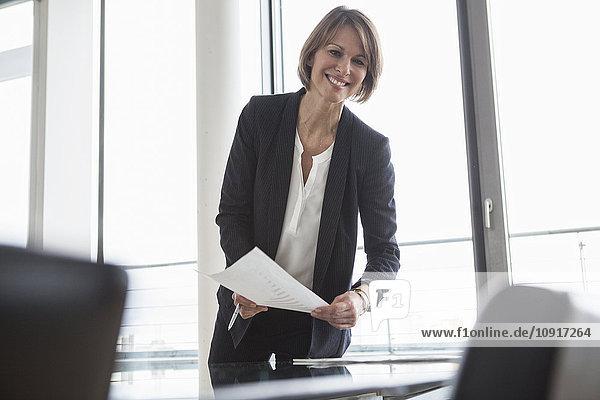 Lächelnde Geschäftsfrau beim Verteilen von Dokumenten im Konferenzraum