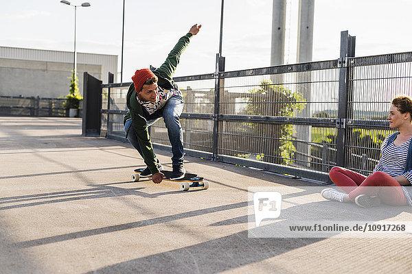 Junges Paar mit Skateboard auf Parkebene